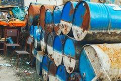 Barrels rostig metall för lotten, stolar, tråd Rostig rund metallcontaine royaltyfri fotografi