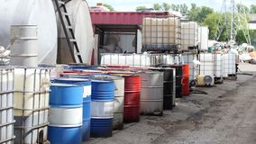 Barrels of used oil stand in a row on the street - recycling. At the processing plant. On the territory of the plant are in a row barrels of used oil - recycling stock footage