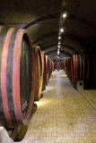 Barrels in a wine-cellar. Antique wooden barrels in an old arched wine cellar Stock Photos