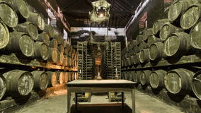 Barrels in the wine cellar with table and candle stock video footage