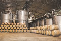 Barrels in the wine cellar. Wine barrels stacked in the wine cellar and large steel tank vessels on a factory,Thailand Stock Photos