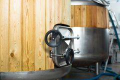 Barrels with wood trimmed for beer fermentation lined in product. Steel barrels with wood trimmed for beer fermentation lined in production hall royalty free stock photo