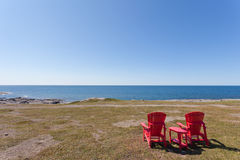 Barren coastal landscape with red wooden chairs. Red Adirondack Chairs overlooking barren coastal landscape of Newfoundland, NL, Canada stock images