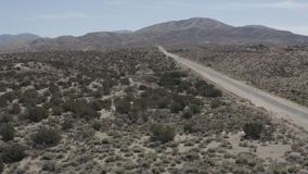 A barren desert land with some small shrubs from the sky. Aerial fly over of a road in a barren desert land with some small shrubs. Need something more specific stock footage