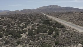 A barren desert land with some small shrubs from the sky. Aerial pullback of a road in a barren desert land with some small shrubs. Need something more specific stock video footage