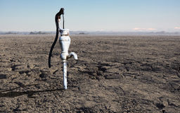 Barren Earth with Dry Water Pump Royalty Free Stock Images