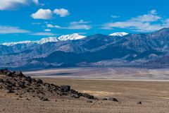 The barren earth and rocks of an arid desert landscape contrasted with high snow-capped mountain peaks royalty free stock images