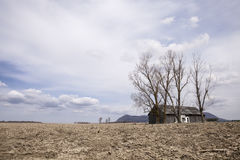 Barren field and barn. Picture of a barren field with big trees and a barn in the background. The picture was taken during spring Stock Image
