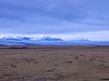 Iceland - Glacier and desert. A barren grassland with the glacier`s cap as a background. Thick and dark clouds are coming closer. Glacier covered in the shadow royalty free stock photo