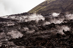 Barren lava fields steaming in light rain with green volcano slo Stock Photos