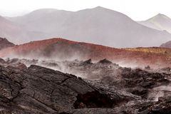 Barren lava fields steaming in light rain with volcanoes in back Royalty Free Stock Photography