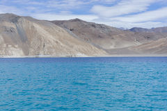 Barren mountains in backdrop of blue lake Stock Image