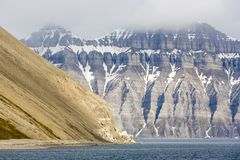 Barren mountains with snow remains seen in Spitsbergen. From the sea Stock Images