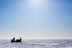 Barren Snow Landscape. A barren flat winter landscape with two people and snowmobiles Royalty Free Stock Photography