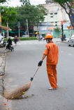 Barrendero de calle en la naranja, Vietnam Imágenes de archivo libres de regalías