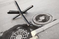 Barrera de acero negra de la calle en el camino urbano del asfalto foto de archivo