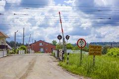 Barrera ferroviaria abierta con las señales de tráfico en un pequeño pueblo en Ucrania fotos de archivo