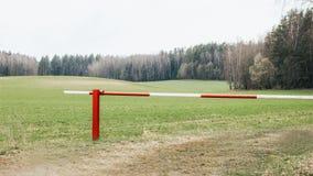 Barrera roja y blanca cerrada en la entrada del bosque fotografía de archivo