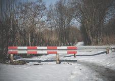 Barrera a través de un camino nevoso del invierno Fotografía de archivo libre de regalías
