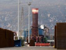 Barres d'acier, matériaux semi de finition, dans une rangée en dehors d'une usine de fabrication avec une grande cheminée Image libre de droits