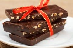 Barres de chocolat avec des écrous attachés avec le ruban rouge sur la soucoupe blanche Photo stock