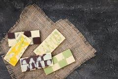 Barres de chocolat crues colorées sur le panneau en bois, fond foncé Photo stock