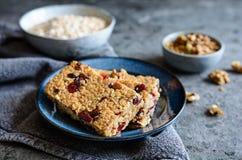 Barres de granola avec des canneberges, des noix, des graines de tournesol et des raisins secs photos stock