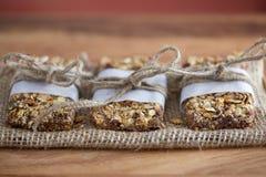 Barres de granola rustiques enveloppées avec la ficelle sur la toile de jute BG rouge Photographie stock libre de droits