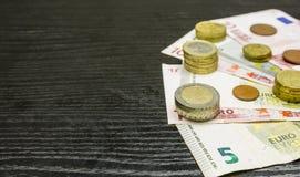 Barres des pièces de monnaie sur des billets de banque - euro devise Photos stock