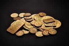 Barres et pièces de monnaie d'or jaune d'isolement sur le fond noir photographie stock