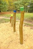 Barres horizontales en acier sur les piliers en bois chez le terrain de jeu des enfants Sable orange au-dessous des barres, parc  Photo libre de droits