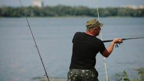 Barretta di lancio del pescatore in un fiume stock footage