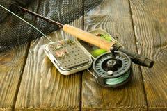 Barretta di pesca con la mosca, scatola delle mosche e un guadino sulla vecchia tavola di legno Tutto pronto per pescare fotografia stock libera da diritti