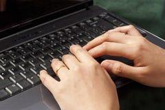 Barrette femminili che digitano su un computer portatile nero Fotografia Stock Libera da Diritti