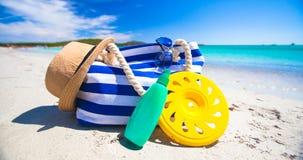 Barrez le sac, le chapeau de paille, le sunblock et la serviette sur le blanc Photo stock
