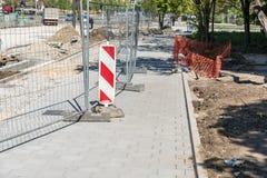 Barriär för plats för konstruktion för vägarbete framåt med det skyddande staketet för metall på den stads- gataskadestå royaltyfria foton
