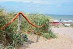 Barriär för rött rep på träpoler framme av gräs på sandstranden med havet i bakgrund royaltyfria bilder