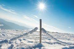 Barrière avec la neige dans le village alpin d'hiver Photos libres de droits