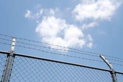 Barrière avec les fils barbelés sur le ciel bleu photographie stock