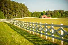 Barrière blanche amenant à une grande grange rouge Images libres de droits