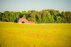 Barrière blanche amenant à une grande grange rouge Photographie stock libre de droits