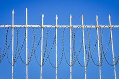 Barrière blanche de fer avec un barbelé contre le ciel bleu Images stock