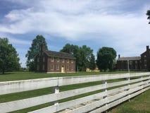 Barrière blanche et vieille maison de brique rouge Photographie stock