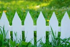 Barrière blanche sur un fond d'herbe verte photographie stock