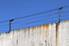 Barrière concrète avec le barbelé sur le fond du bleu lumineux Images libres de droits
