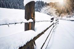 barrière couverte de neige le long de la route dans la hausse d'hiver Photographie stock