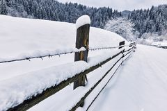 barrière couverte de neige le long de la route dans la hausse d'hiver Images libres de droits