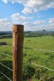 Barrière de courrier et de barbelé le long de terre de pâturage sur le Sussex Southdowns en Angleterre photographie stock