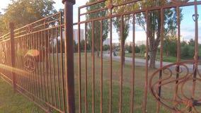 Barrière de fer dans le coucher de soleil banque de vidéos