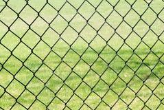 Barrière de maillon de chaîne contre l'herbe Photographie stock libre de droits